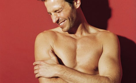 Young man with naked upper part of the body laughing